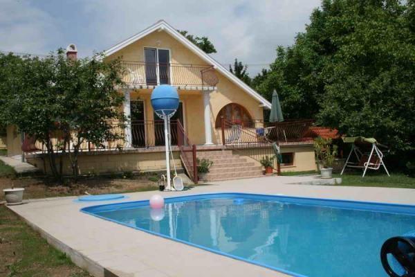 Ein Ferienhaus mit Pool, einem Garten und Seeblick